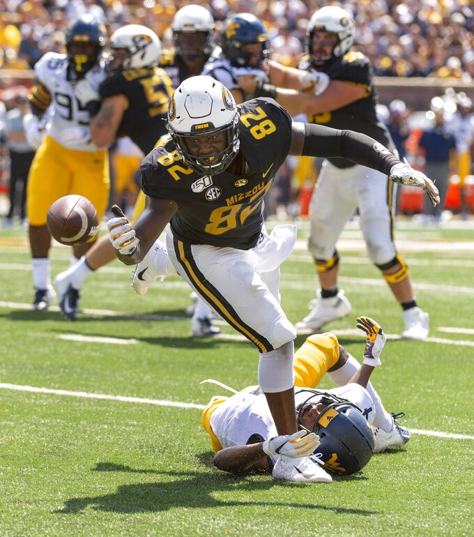 Missouri tight end Daniel Parker Jr., top, drops the ball as he is tripped up by West Virginia safety Josh Norwood, bottom, during the first half of an NCAA college football game Saturday, Sept. 7, 2019, in Columbia, Mo. (AP Photo/L.G. Patterson)