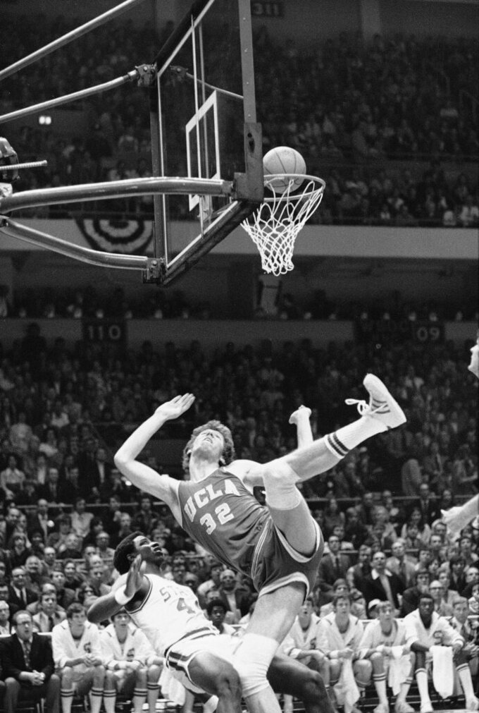 FILE - In this March 23, 1974, file photo, UCLA's Bill Walton (32) falls over North Carolina State's David Thompson during the first period of a semifinal game of the NCAA college basketball championships in Greensboro, N.C. North Carolina State brought UCLA down to earth after seven straight national championships, beating the mighty Bruins 80-77 on David Thompson's crucial points in double overtime in the semifinals of the NCAA college basketball tournament. (AP Photo/File)