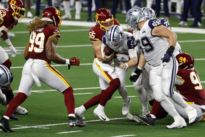 Washington Football Team's Chase Young (99) looks on as Cole Holcomb (55) sacks Dallas Cowboys' Andy Dalton (14) in the second half of an NFL football game in Arlington, Texas, Thursday, Nov. 26, 2020. (AP Photo/Roger Steinman)