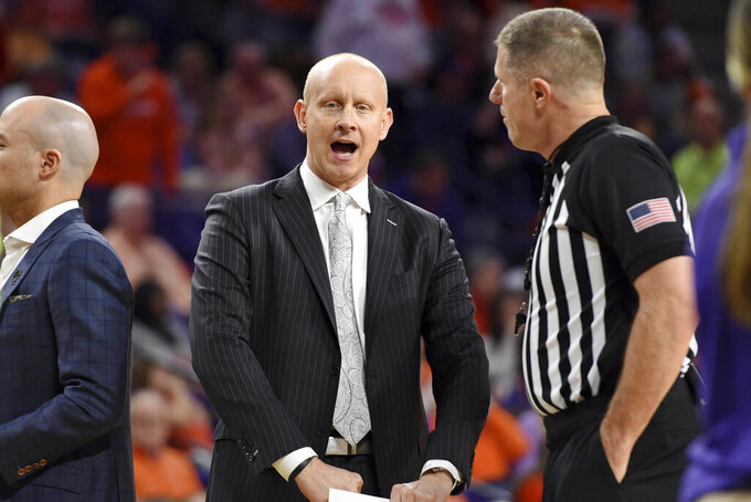 Louisville head coach Chris Mack, left, speaks with an official during the first half of an NCAA college basketball game against Clemson, Saturday, Feb. 15, 2020, in Clemson, S.C. (AP Photo/Richard Shiro)