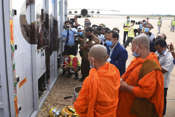 """Neth Pheaktra, center, Spokesmen of Environment Ministry, presides over the blessing of a  container holding Kaavan the elephant during its arrival from Pakistan at the Siem Reap International Airport, Cambodia, Monday, Nov. 30, 2020. Kaavan, dubbed the """"world's loneliest elephant"""" after languishing alone for years in a Pakistani zoo, has arrived in Cambodia where a sanctuary with the much-needed company of other elephants awaits him. (Pool Photo via AP)"""