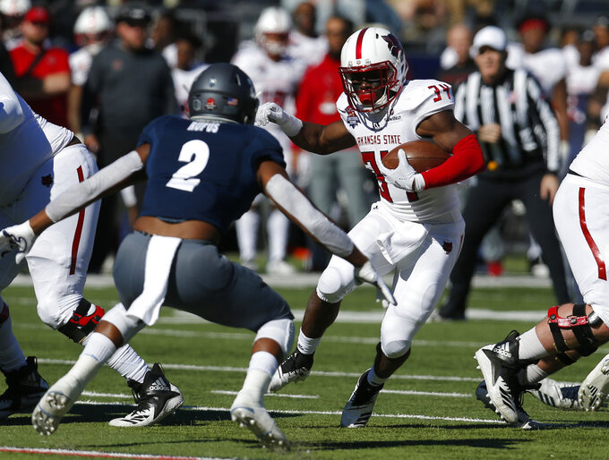 Arkansas State running back Marcel Murray (34) runs for a first down in front of Nevada defensive back Asauni Rufus in the first half of the Arizona Bowl NCAA college football game Saturday, Dec. 29, 2018, in Tucson, Ariz.(AP Photo/Rick Scuteri)