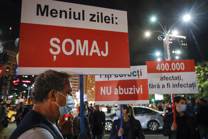 """A protester holds a banner that reads """"Today's Menu: Unemployment"""" as hospitality workers protest against the government's decision for the closure of restaurants, cinemas, theatres and hospitality venues in the capital, for a second time, in Bucharest, Romania, Wednesday, Oct. 7, 2020. Hundreds of Romanian hospitality workers protested Wednesday evening in the capital, Bucharest, against what they describe as the national government's failure to protect their industry from the economic fallout of the coronavirus epidemic in the country.  (AP Photo/Vadim Ghirda)"""