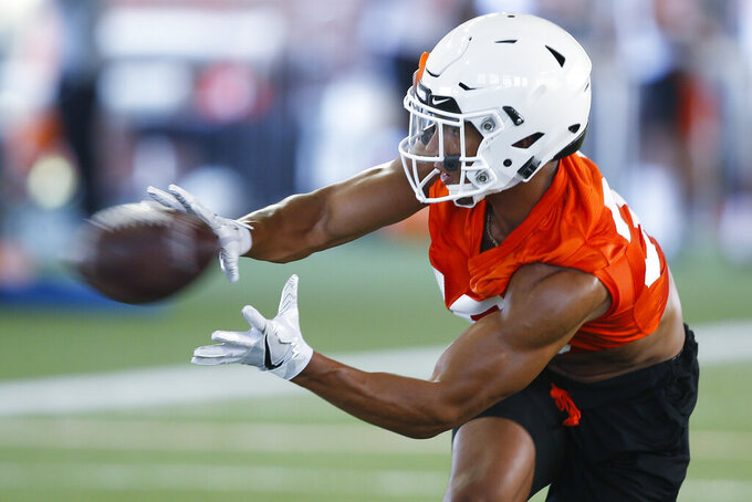 In this Thursday, Aug. 1, 2019 photo, Oklahoma State running back Chuba Hubbard reaches for a ball during NCAA college football practice in Stillwater, Okla. Hubbard was an unknown freshman backup a year ago. This season, he's a preseason All-Big 12 pick. (AP Photo/Sue Ogrocki)
