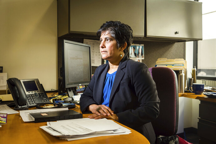 In this April 16, 2019 photo, Dr. Hina Shah poses at Golden Gate University in San Francisco, where she is a professor and the director of the Women's Employment Rights Clinic, which represents low-wage workers on issues of wage theft, discrimination and harassment. Residential senior care homes are treating workers as indentured servants – and profiting handsomely. The profit margins can be huge and, for violators of labor laws, hinge on the widespread exploitation of thousands of caretakers, many of them poor immigrants effectively earning $2 to $3.50 an hour to work around the clock.