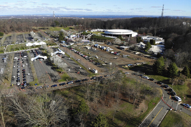 A line of cars waits to get into a drive-though COVID-19 testing site at the PNC Bank Arts Center in Holmdel, N.J., Tuesday, March 24, 2020. (AP Photo/Seth Wenig)
