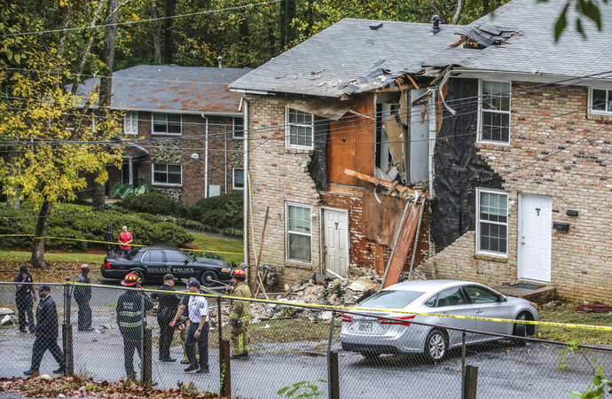 Fire officials look at the scene where an airplane crashed into an apartment complex, Wednesday, Oct. 30, 2019, in Atlanta. (John Spink/Atlanta Journal-Constitution via AP)