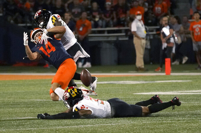 Maryland defensive back Jakorian Bennett, right, breaks up a pass intended for Illinois wide receiver Casey Washington as Nick Cross (3) also defends during the first half of an NCAA college football game Friday, Sept. 17, 2021, in Champaign, Ill. (AP Photo/Charles Rex Arbogast)