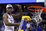 FILE - In this March 25, 2018, file photo, Kansas' Silvio De Sousa celebrates by cutting down the net after Kansas defeated Duke 85-81 in a regional final in the NCAA men's college basketball tournament in Omaha, Neb. The storied Jayhawks program faces serious questions about whether it will remain eligible for the postseason come March 2020 in the wake of NCAA allegations of recruiting fraud that could sink both the program and its Hall of Fame coach, Bill Self. The Kansas scenario, involving payments to recruits Billy Preston and Silvio De Sousa, could have damaging repercussions. (AP Photo/Charlie Neibergall, File)