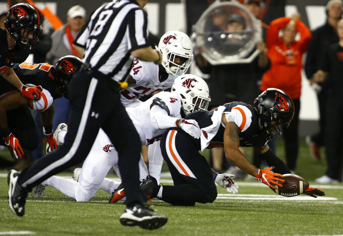 Oregon State's Trevon Bradford, right, grabs a fumble in front of Washington State's Jalen Thompson (34) and Marcus Strong (4) during the first half of an NCAA college football in Corvallis, Ore., Saturday, Oct. 6, 2018. (AP Photo/Timothy J. Gonzalez)