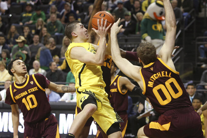 Oregon's Payton Pritchard, center, is fouled while going to the basket between Arizona State's Jaelen House, left, and Mickey Mitchell, right, during the second half of an NCAA college basketball game in Eugene, Ore., Saturday, Jan. 11, 2020. (AP Photo/Chris Pietsch)