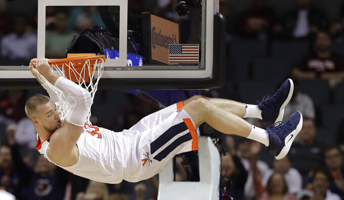 Virginia's Jack Salt (33) hangs from the rim after a dunk against North Carolina State during the second half of an NCAA college basketball game in the Atlantic Coast Conference tournament in Charlotte, N.C., Thursday, March 14, 2019. Salt was called for a technical foul on the play. (AP Photo/Chuck Burton)