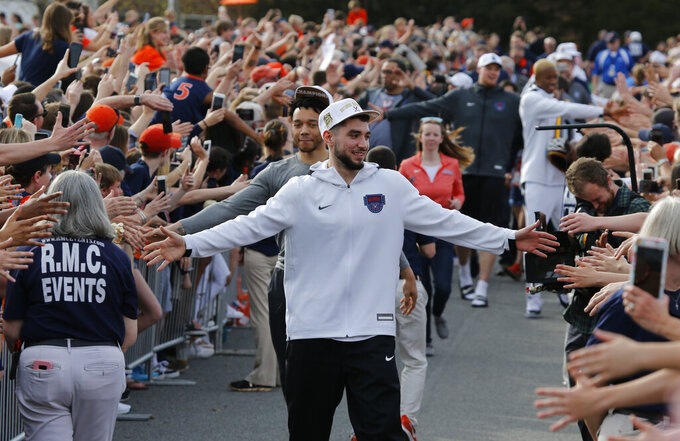 Ty Jerome and other members of the Virginia basketball team are welcomed by fans as they return home after their win of the championship in the Final Four NCAA college basketball tournament against Texas Tech, in Charlottesville, Va., Tuesday, April 9, 2019. (AP Photo/Steve Helber)