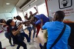 Government supporters, left and front, fight with a member of the opposition who is awaiting the arrival of opposition leader Juan Guaido at the Simon Bolivar International Airport in La Guaira, Venezuela, Tuesday, Feb. 11, 2020. Guaido is expected to return to Venezuela from a tour of nations that back his effort to oust socialist leader Nicolás Maduro. (AP Photo/Matias Delacroix)