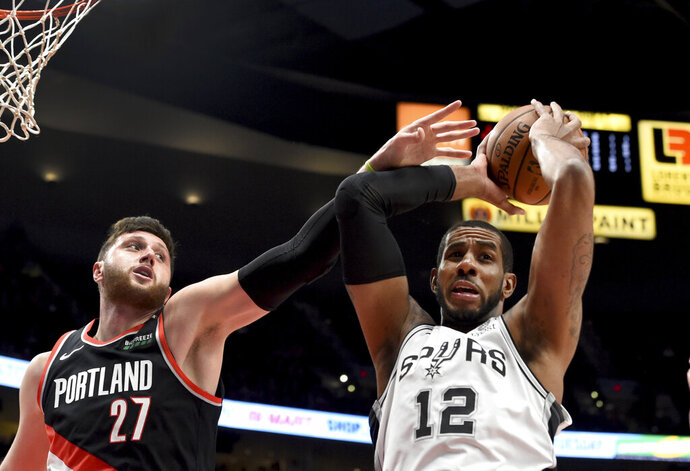 San Antonio Spurs center LaMarcus Aldridge, right, grabs a rebound in front of Portland Trail Blazers center Jusuf Nurkic during the first half of an NBA basketball game in Portland, Ore., Thursday, Feb. 7, 2019. (AP Photo/Steve Dykes)