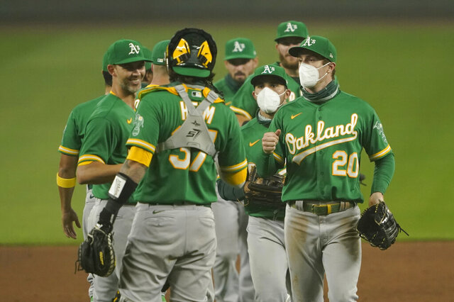 Oakland Athletics outfielders Mark Canha (20) and Ramon Laureano, second from right, wear masks as they greet teammates after they defeated the Seattle Mariners in the second baseball game of a doubleheader, Monday, Sept. 14, 2020, in Seattle. Both games were played in air smoky from wildfires in Oregon, Washington, and California. (AP Photo/Ted S. Warren)