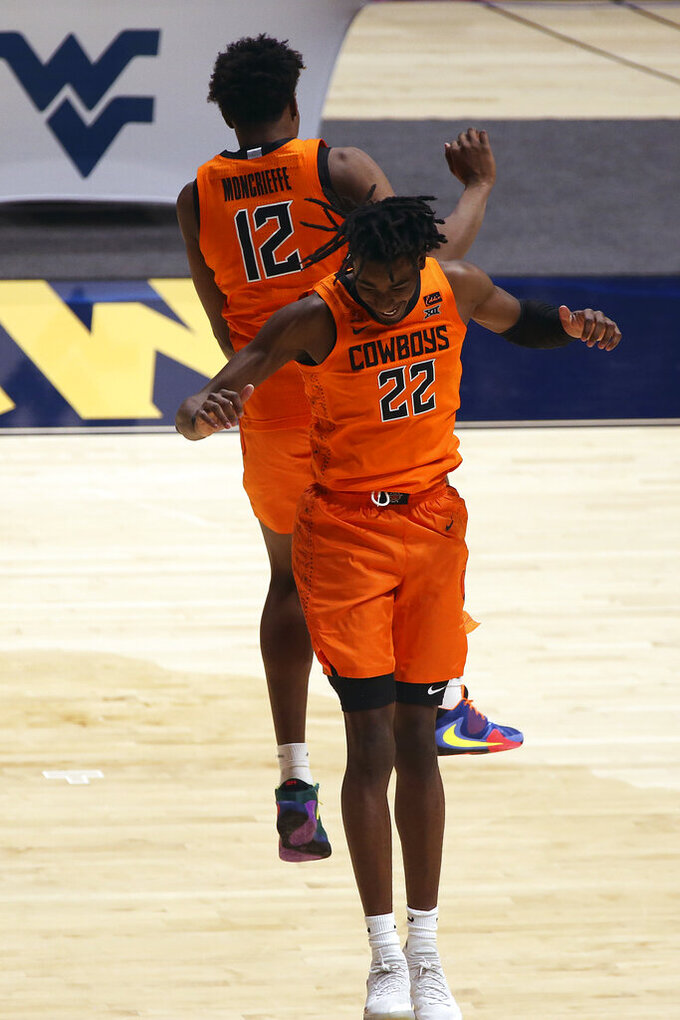 Oklahoma State forwards Matthew-Alexander Moncrieffe (12) and Kalib Boone (22) celebrate after a win against West Virginia  in an NCAA college basketball game Saturday, March 6, 2021, in Morgantown, W.Va. (AP Photo/Kathleen Batten)