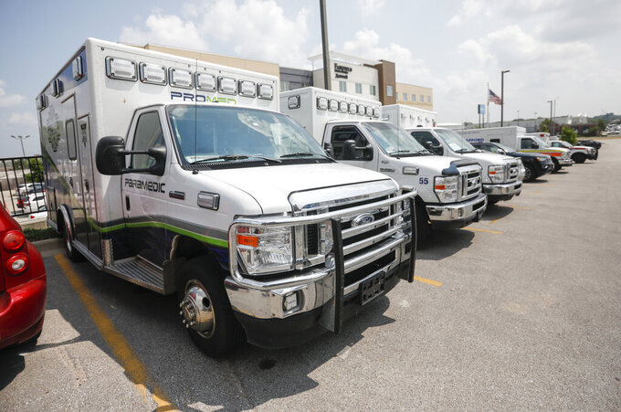 Ambulance crews unload equipment at the DoubleTree Hotel on Friday, July 23, 2021, in Springfield, Mo. The crews are part of a medical team that was sent to Springfield to help transport COVID-19 patients in the area. (Andrew Jansen/The Springfield News-Leader via AP)