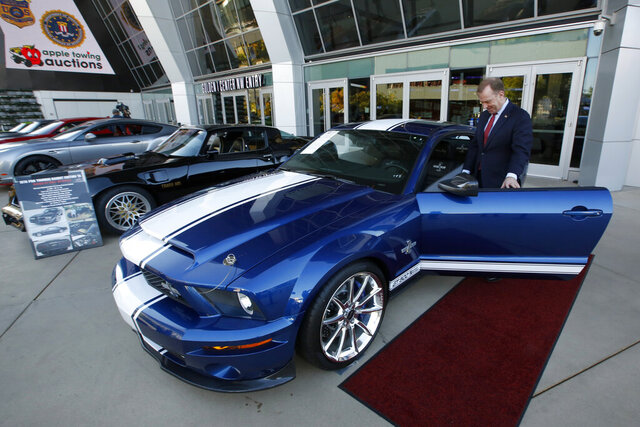 File - In this Oct. 23, 2019, file photo, McGregor Scott, the U.S. Attorney for the Eastern District of California, looks over a 2007 Ford Shelby GT500 displayed in Sacramento, Calif., that was among the vehicles seized by the federal government to be auctioned off. The cars belonged to owners of a San Francisco Bay Area solar energy company that have pleaded guilty for participating in what federal prosecutors called a massive Ponzi scheme that defrauded investors of $1 billion. Jeff and Paulette Carpoff entered pleas Friday, Jan. 24, 2020, involving the scam that could result in up to 30 years in prison for him, and up to 15 years in prison for her. (AP Photo/Rich Pedroncelli, File)
