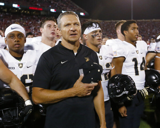 FILE - In this Sept. 22, 2018, file photo, Army coach Jeff Monken stands with his team after an NCAA college football game against Oklahoma in Norman, Okla. Monken and his staff have been crisscrossing the country in search of new talent. He says the academy-record 11 wins last season and a final ranking of No. 19 in the AP Top 25 have helped, but he stills needs to explain what West Point is to many potential recruits. (AP Photo/Sue Ogrocki, File)