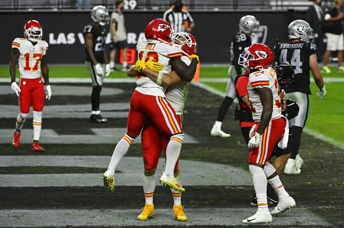 Kansas City Chiefs tight end Travis Kelce embraces wide receiver Tyreek Hill (10) after Kelce scored a touchdown against the Las Vegas Raiders during the second half of an NFL football game, Sunday, Nov. 22, 2020, in Las Vegas. (AP Photo/David Becker)