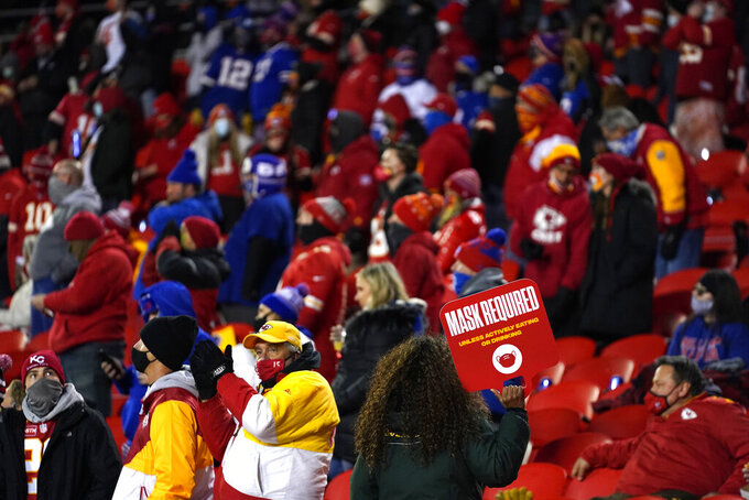 "An usher holds a ""mask required"" sign in the stands during the first half of the AFC championship NFL football game between the Kansas City Chiefs and the Buffalo Bills, Sunday, Jan. 24, 2021, in Kansas City, Mo. (AP Photo/Jeff Roberson)"