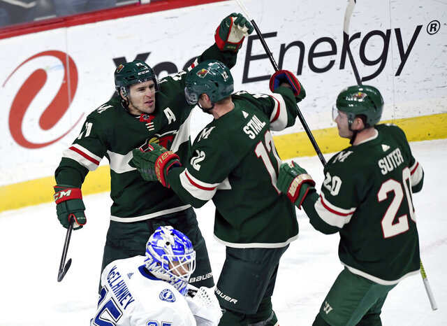 Minnesota Wild's Eric Staal (12) and Ryan Suter (20) congratulate Zach Parise (11) on his goal as Tampa Bay Lightning goaltender Curtis McElhinney (35) watches during the first period of an NHL hockey game Thursday, Jan. 16, 2020, in St. Paul, Minn. (AP Photo/Hannah Foslien)