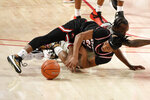 Western Kentucky guard Kenny Cooper, bottom, and Houston guard DeJon Jarreau chase a loose ball during the first half of an NCAA college basketball game, Thursday, Feb. 25, 2021, in Houston. (AP Photo/Eric Christian Smith)