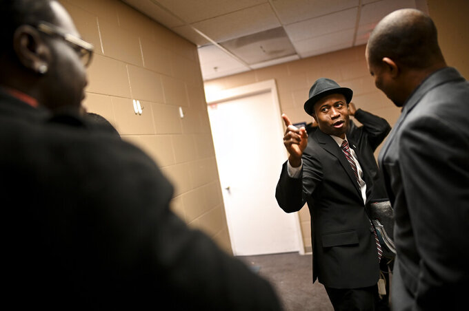 Erik Anderson, left, of Trenton, N.J., is greeted by Brooklyn Center Mayor-elect Mike Elliott, center, before Elliot's inauguration ceremony, Wednesday, Jan. 2, 2019, at the Brooklyn Center Community Center, in Brooklyn Center, Minn. Elliott is the city's first Black and first Liberian American mayor. Elliott, who emigrated from Liberia as a child, is finding just how difficult it is to turn the page on the nation's racial history as he handles the fallout from a police shooting.(Aaron Lavinsky/Star Tribune via AP)