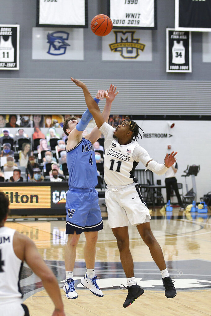 Providence's A.J. Reeves (11) blocks a shot by Villanova's Chris Arcidiacono (4) during an NCAA college basketball game in Providence, R.I., Saturday, March 6, 2021. (AP Photo/Stew Milne)