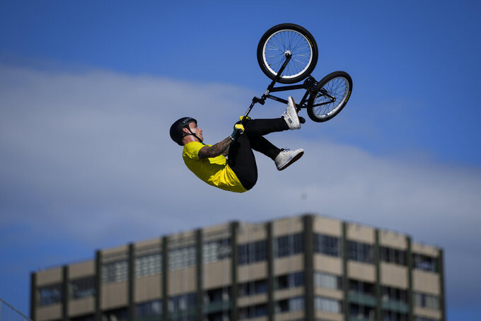 Logan Martin of Australia makes a jump with a nearby apartment building seen in the background, during a BMX Freestyle training session at the 2020 Summer Olympics, Tuesday, July 27, 2021, in Tokyo, Japan. (AP Photo/Ben Curtis)