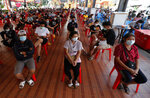 People wait to receive the Sinovac COVID-19 vaccine in Bangkok, Thailand, Monday, April 12, 2021. Thailand's Health Ministry warned Sunday that restrictions may need to be tightened to slow the spread of a fresh coronavirus wave, as the country hit a daily record for new cases. (AP Photo/Sakchai Lalit)