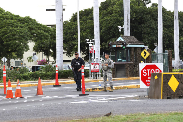 FILE - In this Dec. 4, 2019 file photo security stand outside the main gate at Joint Base Pearl Harbor-Hickam in Hawaii. A live mortar round was found in a vehicle late Tuesday at a gate to the sprawling Pearl Harbor military base, shutting down the base for hours and leading three people to be taken into custody, military officials said Wednesday, Jan. 15, 2020. A base spokesman said that he doesn't know what the trio planned to do or where they wanted to go. (AP Photo/Caleb Jones, File)