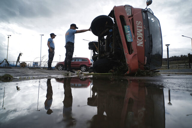 Police inspect a truck that was damaged as Typhoon Kammuri slammed Legazpi city, Albay province, southeast of Manila, Philippines, Tuesday, Dec. 3, 2019. Typhoon Kammuri barreled across the Philippine archipelago with fierce rain and wind Tuesday, leaving at least four people dead, forcing tens of thousands of villagers to abandon high-risk communities and prompting officials to shut Manila's international airport. (AP Photo)