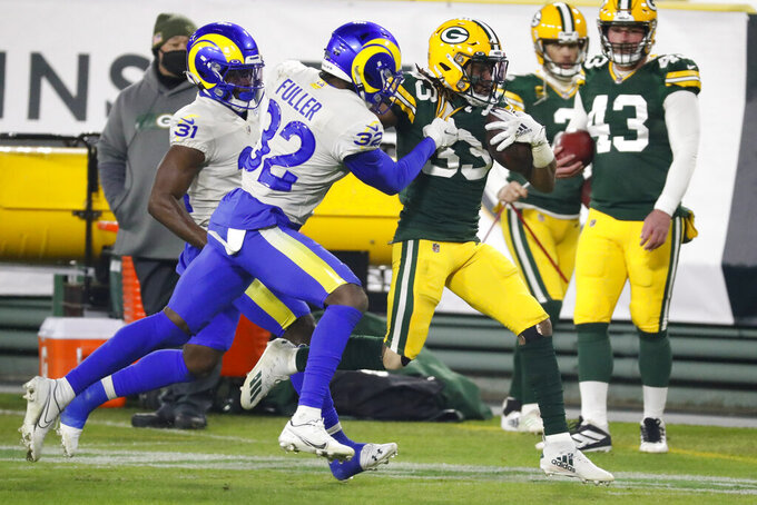 Los Angeles Rams' Jordan Fuller (32) tackles Green Bay Packers' Aaron Jones (33) during the second half of an NFL divisional playoff football game Saturday, Jan. 16, 2021, in Green Bay, Wis. (AP Photo/Mike Roemer)
