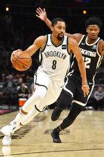 Brooklyn Nets guard Spencer Dinwiddie (8) drives as Atlanta Hawks forward Cam Reddish defends during the first half of an NBA basketball game Wednesday, Dec. 4, 2019, in Atlanta. (AP Photo/John Amis)