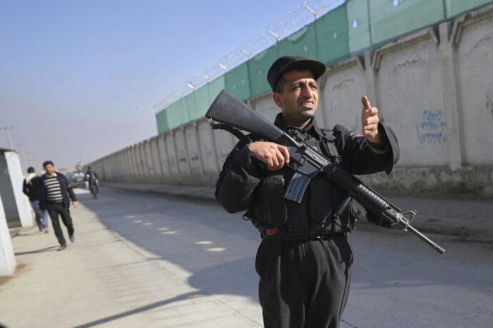 A police officer stops people and vehicles at a checkpoint near the site of a shootout in Kabul, Afghanistan, Monday, Dec. 2, 2019. An Afghan official says a gunman has opened fire on a vehicle in the capital, Kabul, killing two intelligence officials and wounding three others. (AP Photo/Altaf Qadri)