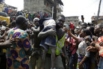 A body of a child is recovered from the rubble of a collapsed building in Lagos, Nigeria, Wednesday March 13, 2019. Rescue efforts are underway in Nigeria after a three-story school building collapsed while classes were in session. (AP Photo/Sunday Alamba)