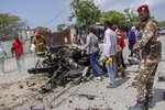 Security forces and civilians stand near the wreckage after a suicide car bomb attack that targeted the city's police commissioner in Mogadishu, Somalia Saturday, July 10, 2021. At least nine people are dead and others wounded after the large explosion, a health official at the Medina hospital said, noting that the toll reflected only the dead and wounded brought there. (AP Photo/Farah Abdi Warsameh)