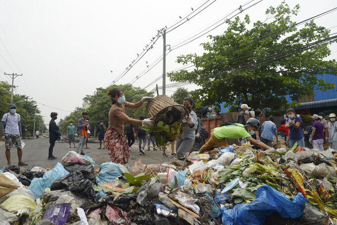 """Anti-coup protesters throw garbage to block a road as a form of a """"silent protest"""" in Yangon, Myanmar on Tuesday, March 30, 2021. At least 510 protesters have been killed since the coup, as of Tuesday, according to Myanmar's Assistance Association for Political Prisoners, which says the actual toll is likely much higher. (AP Photo)"""