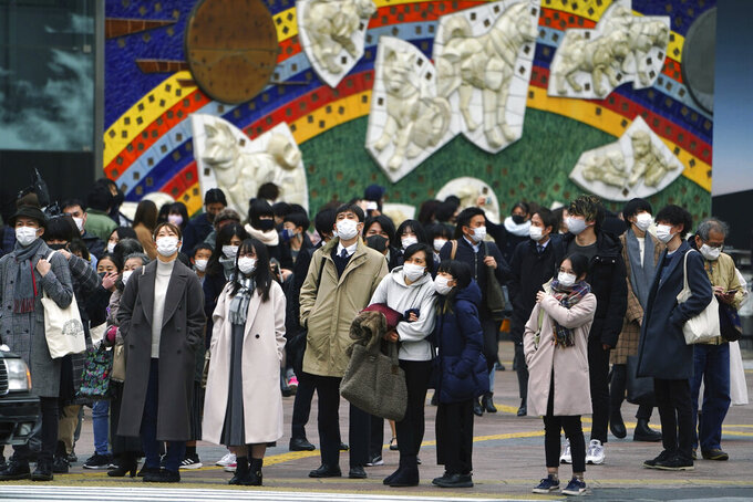 People wearing protective masks to help curb the spread of the coronavirus wait for traffic light to walk along pedestrian crossings in the Shibuya area of Tokyo Tuesday, Jan. 5, 2021. Japanese Prime Minister Yoshihide Suga says vaccine approval is being speeded up to curb the spread of the coronavirus, and he promised to consider declaring a state of emergency. The Japanese capital confirmed more than 1200 new coronavirus cases on Tuesday. (AP Photo/Eugene Hoshiko)
