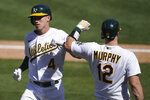 Oakland Athletics' Jake Lamb, left, is congratulated by Sean Murphy after hitting a solo home run against the Seattle Mariners during the seventh inning of a baseball game in Oakland, Calif., Sunday, Sept. 27, 2020. (AP Photo/Jeff Chiu)