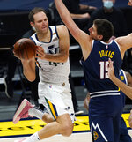 Utah Jazz forward Bojan Bogdanovic, left, passes the ball as he drives by Denver Nuggets center Nikola Jokic in the first half of an NBA basketball game Sunday, Jan. 17, 2021, in Denver. (AP Photo/David Zalubowski)