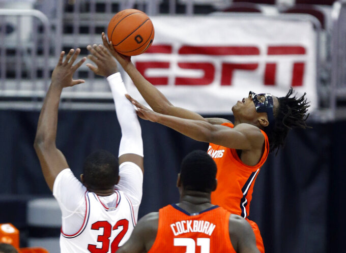Illinois guard Ayo Dosunmu, right, goes up to shoot in front of teammate center Kofi Cockburn and Ohio State forward E.J. Liddell, left, during the first half of an NCAA college basketball game in Columbus, Ohio, Saturday, March 6, 2021. (AP Photo/Paul Vernon)