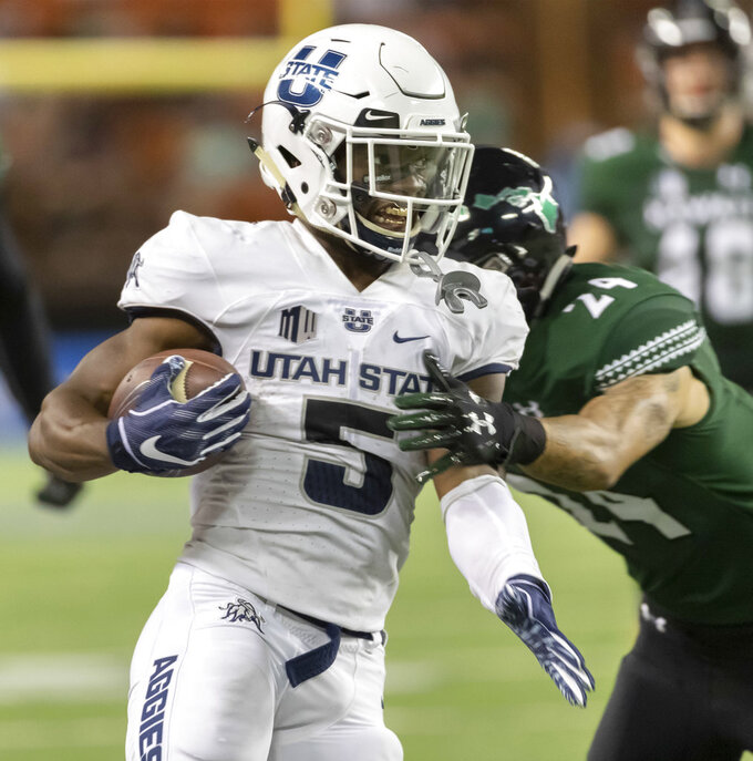 Utah State running back Darwin Thompson (5) runs as Hawaii defensive back Kai Kaneshiro (24) attempts to wrap Thompson up in the first half of an NCAA college football game, Saturday, Nov. 3, 2018, in Honolulu. (AP Photo/Eugene Tanner)