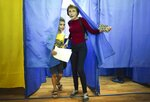 A woman and a boy leave a booth at a polling station during at a parliamentary election in Kiev, Ukraine, Sunday, July 21, 2019. The party of new President Volodymyr Zelenskiy is widely predicted to get the largest share of votes in Sunday's election. (AP Photo/Evgeniy Maloletka)