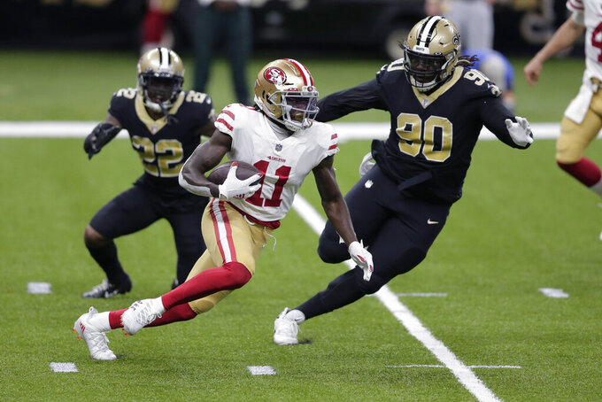 San Francisco 49ers wide receiver Brandon Aiyuk (11) carries past New Orleans Saints defensive tackle Malcom Brown (90) and safety Chauncey Gardner-Johnson (22) in the first half of an NFL football game in New Orleans, Sunday, Nov. 15, 2020. (AP Photo/Brett Duke)