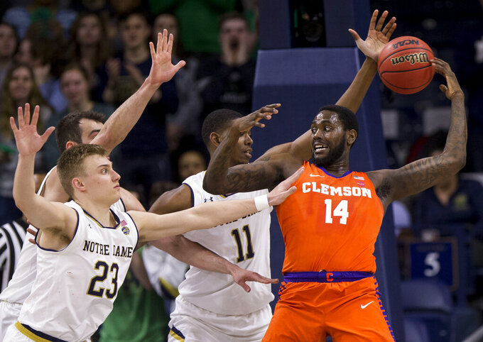 Clemson's Elijah Thomas (14) loses control of the ball under pressure from Notre Dame's Dane Goodwin (23), John Mooney and Juwan Durham (11) during the second half of an NCAA college basketball game Wednesday, March 6, 2019, in South Bend, Ind. Clemson won 64-62. (AP Photo/Robert Franklin)