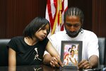 FILE - In this May 18, 2010 file photo, Dominika Stanley, left, the mother of 7-year-old Aiyana Stanley-Jones, sits next to Aiyana's father Charles Jones, who holds a photo of her in Southfield, Mich. The family sued the city and was awarded more than $8 million after she was shot to death during a 2010 police raid at her home while sleeping on a sofa. (AP Photo/Carlos Osorio, File)