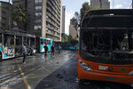 Buses that were set alight by demonstrators during last night's protests stand on a street in Santiago, Chile, Saturday, Oct. 19, 2019. The protests started on Friday afternoon when high school students flooded subway stations, jumping turnstiles, dodging fares and vandalizing stations as part of protests against a fare hike, but by nightfall had extended throughout Santiago with students setting up barricades and fires at the entrances to subway stations, forcing President Sebastian Pinera to announce a state of emergency and deploy the armed forces into the streets. (AP Photo/Esteban Felix)